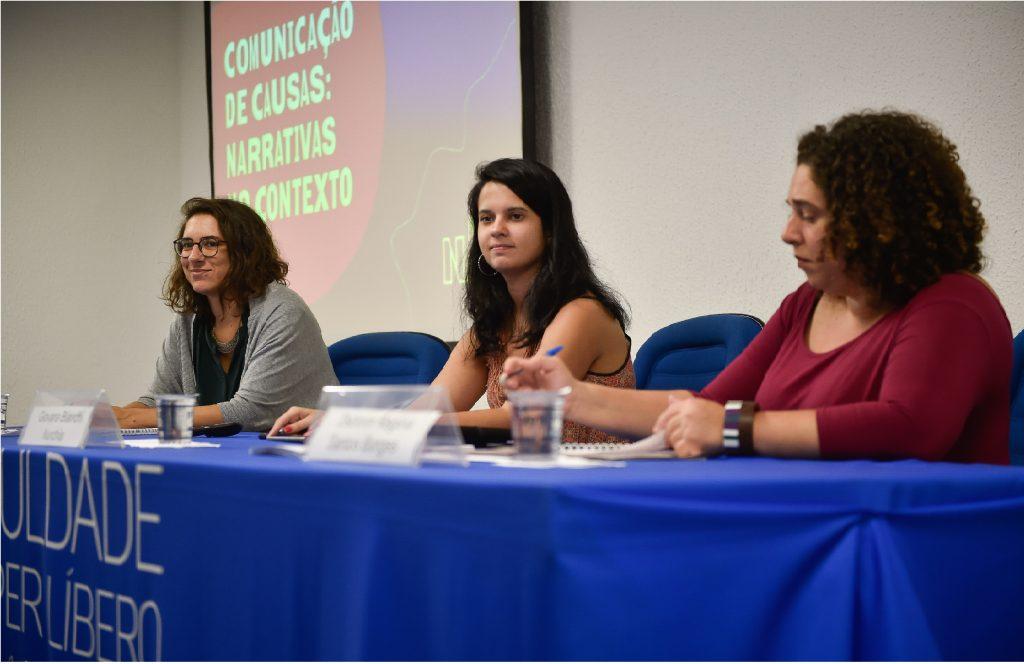 Giovana Bianchi, Laura Leal, Débora Borges estão sentadas em uma bancada. Ao fundo está projetado em um painel: comunicação de causas: narrativas