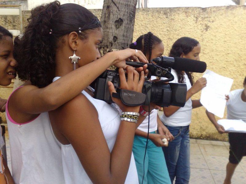 No centro da imagem um jovem segura uma filmadora. Outros jovens aparecem ao fundo.